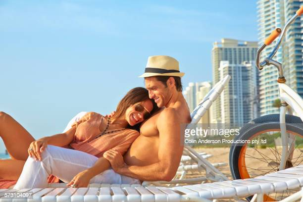 Hispanic couple relaxing on beach