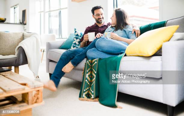 Hispanic couple relaxing on sofa and drinking coffee.