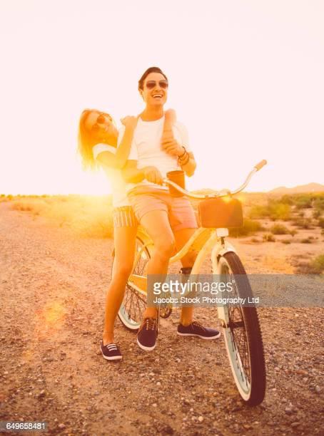 Hispanic couple riding bicycle on dirt road
