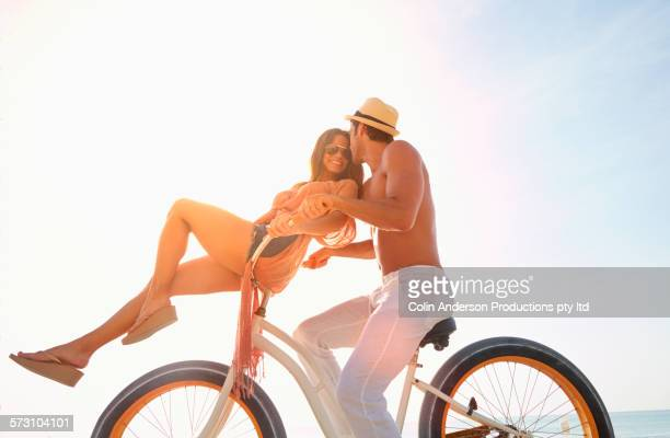 Hispanic couple riding bicycle outdoors