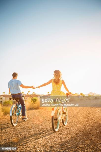 Hispanic couple riding bicycles on dirt road