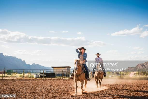 Hispanic couple riding horses on ranch