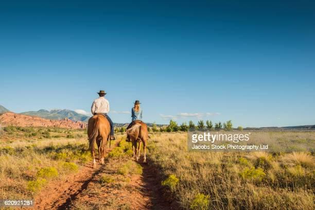 hispanic couple riding horses on rural path - moab utah stock-fotos und bilder
