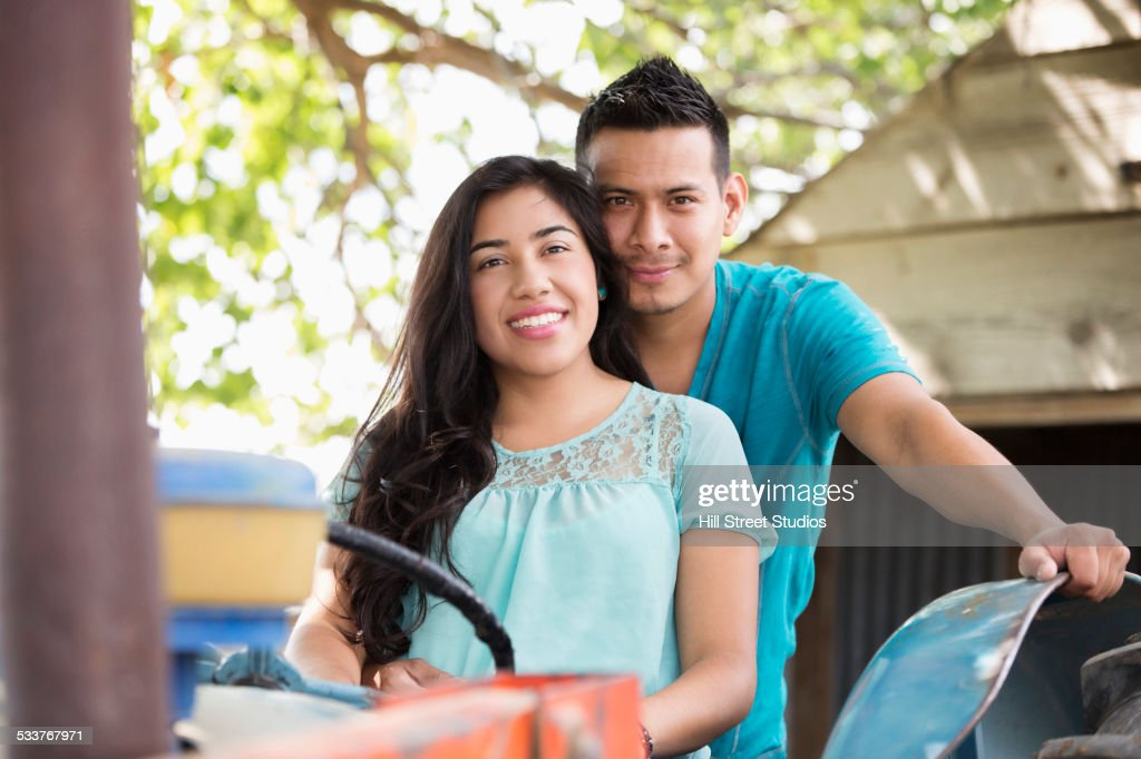Hispanic couple riding tractor on ranch : Foto stock