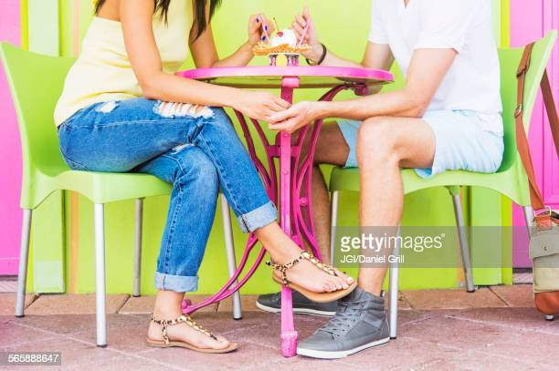 Hispanic couple sharing ice cream sundae