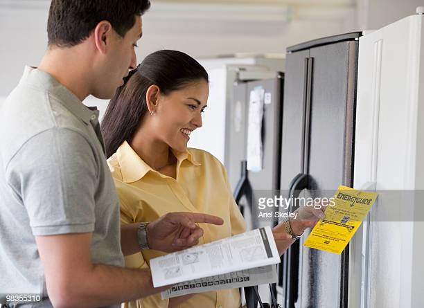 hispanic couple shopping for refrigerator - appliance stock pictures, royalty-free photos & images