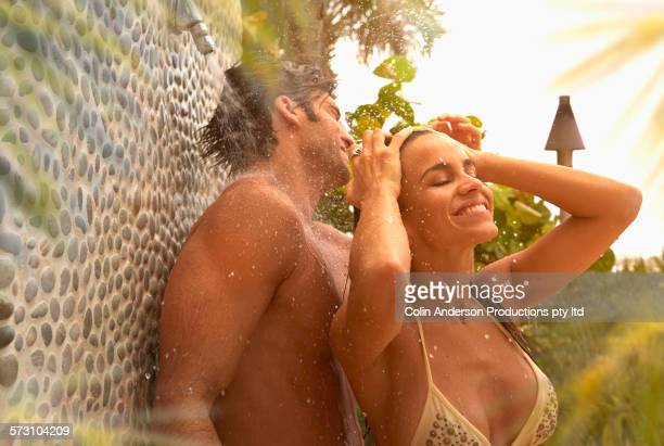 Hispanic couple showering in bathing suits outdoors