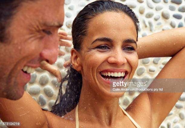 hispanic couple showering in bathing suits outdoors - pareja ducha fotografías e imágenes de stock