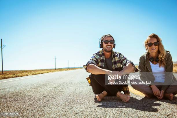 Hispanic couple sitting barefoot in middle of road