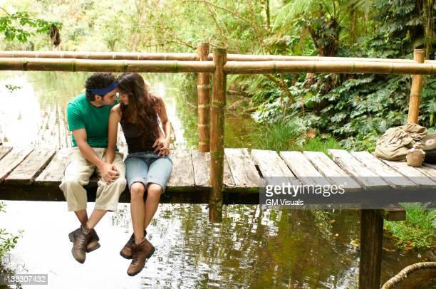 Hispanic couple sitting holding hands on wooden walkway