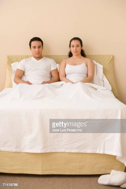 Hispanic couple sitting in bed