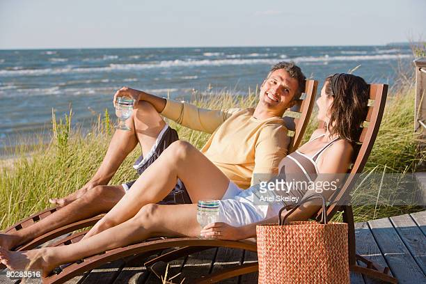 Hispanic couple sitting in deck chairs