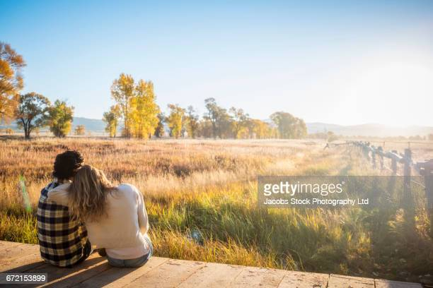 hispanic couple sitting on footbridge over marsh - three quarter length stock pictures, royalty-free photos & images