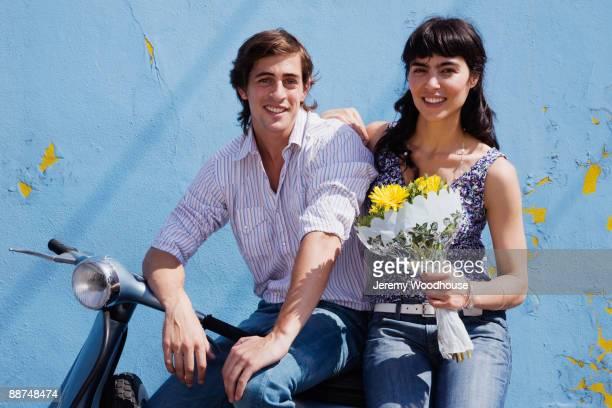 Hispanic couple sitting on scooter