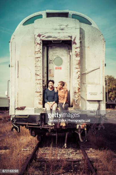 Hispanic couple sitting on train exterior
