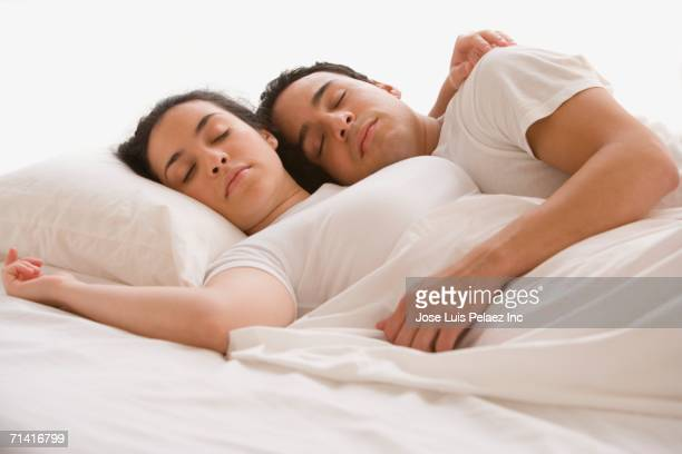 hispanic couple sleeping - romantic young couple sleeping in bed stock photos and pictures