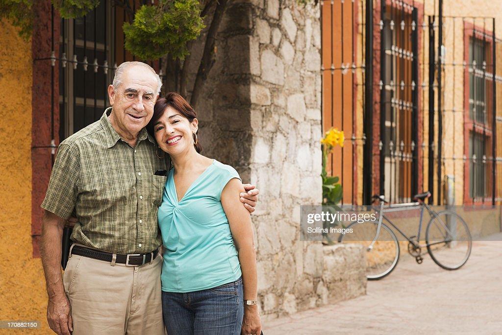 Hispanic couple smiling on city street : Stock Photo
