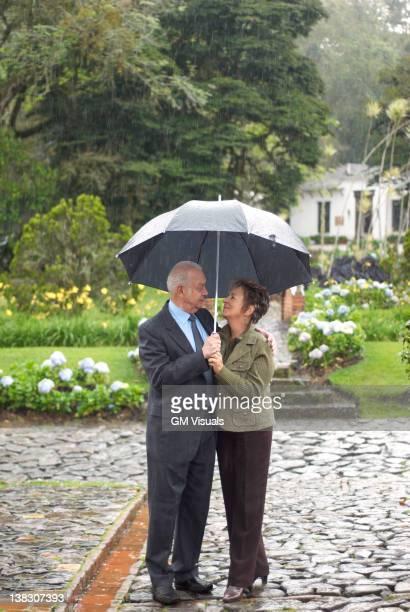 Hispanic couple standing together under umbrella