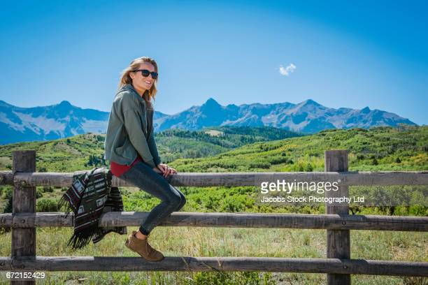 Hispanic couple straddling wooden fence near mountains
