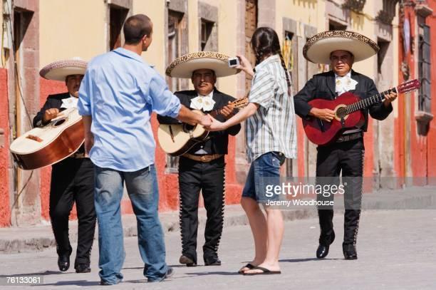 Hispanic couple taking photograph of Mariachi band