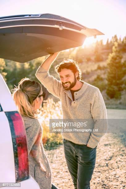 Hispanic couple talking at car hatch