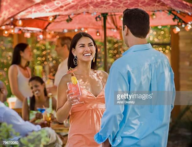 Hispanic couple talking at party