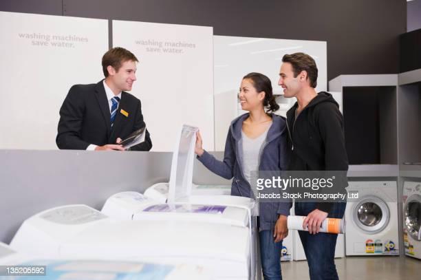 Hispanic couple talking to salesman in appliance department