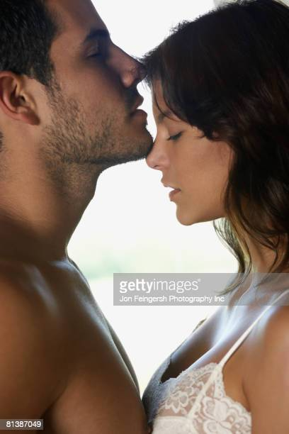 Hispanic couple touching faces