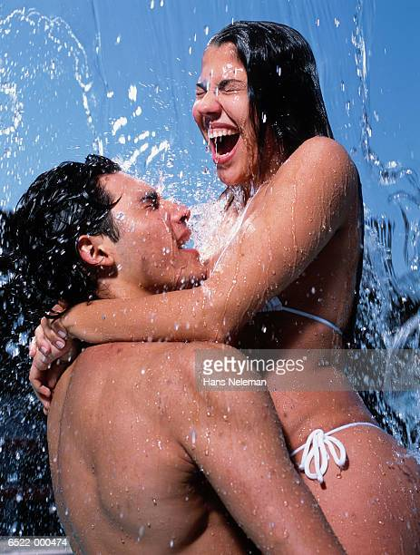 hispanic couple under shower - couples showering together stock photos and pictures