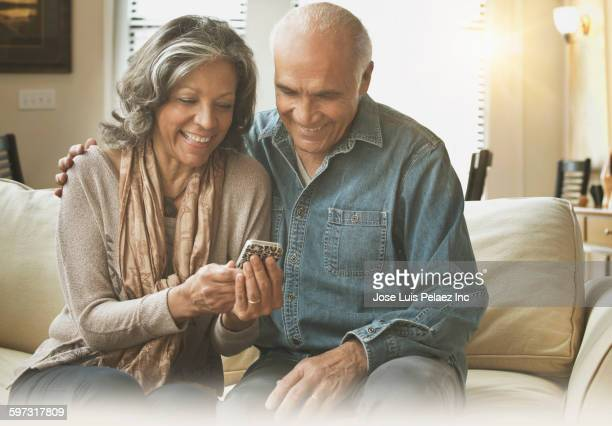 Hispanic couple using cell phone on sofa