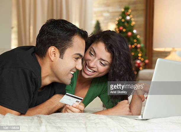 Hispanic couple using credit card online at Christmastime
