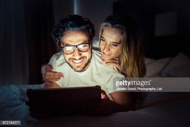 Hispanic couple using digital tablet in bed at night