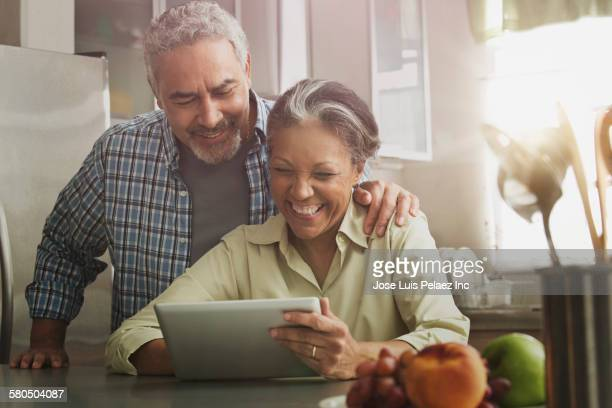 hispanic couple using digital tablet in kitchen - 60 69 jaar stockfoto's en -beelden
