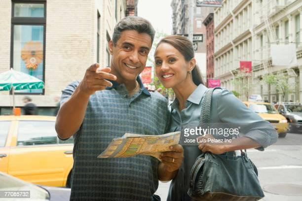 hispanic couple using street map - homens de idade mediana imagens e fotografias de stock
