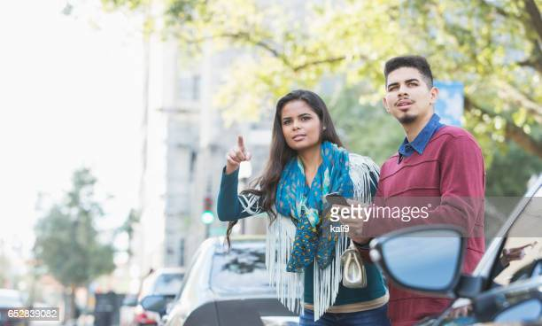 Hispanic couple waiting for a car to pick them up