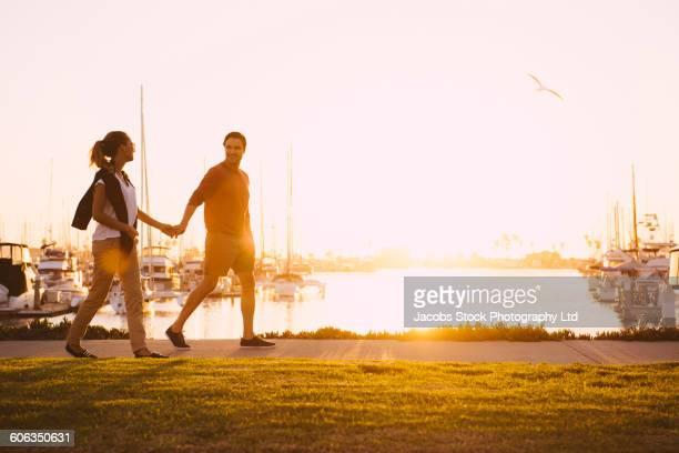 Hispanic couple walking at marina