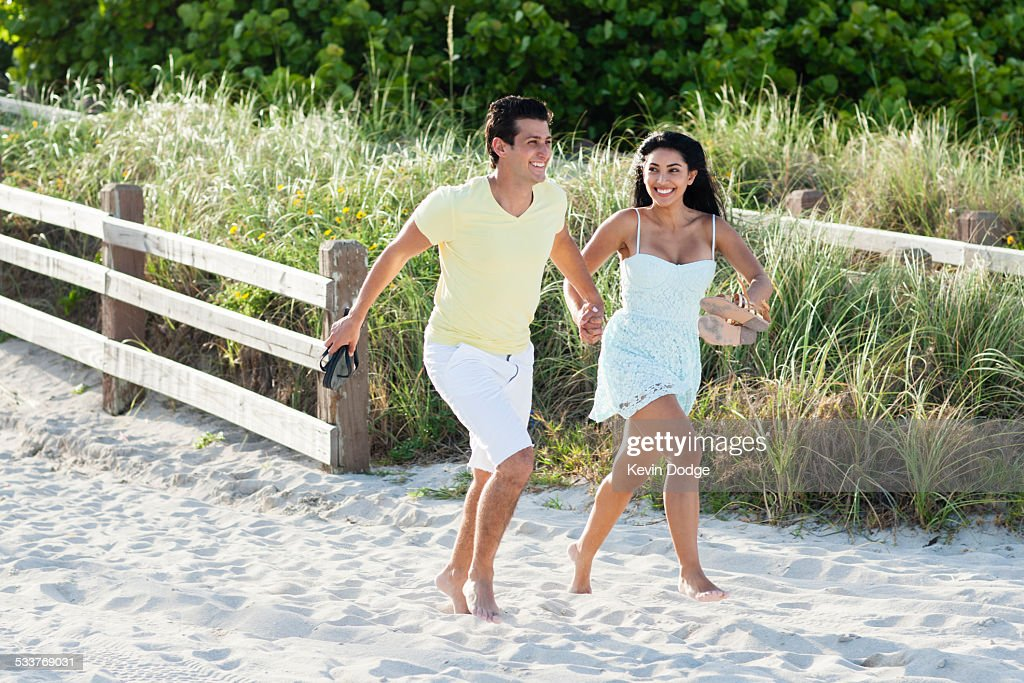 Hispanic couple walking on beach : Foto stock