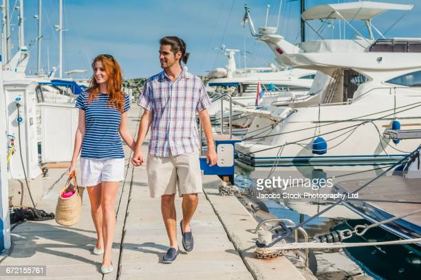 Hispanic Couple walking on dock at marina