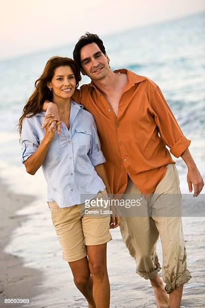 Hispanic couple walking on the beach.