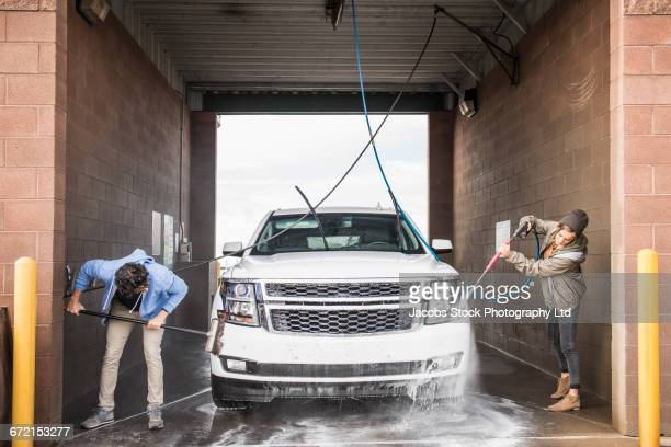 hispanic couple washing car at self-serve car wash - couples showering stock pictures, royalty-free photos & images