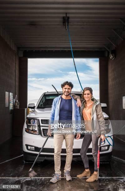 hispanic couple washing car posing at self-serve car wash - car wash brush stock pictures, royalty-free photos & images