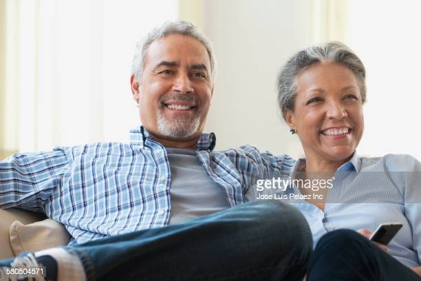 Hispanic couple watching television on sofa