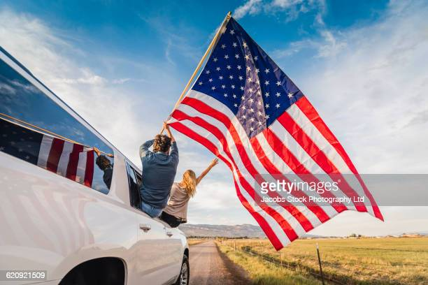 hispanic couple waving american flag out car window - independence day holiday stock photos and pictures