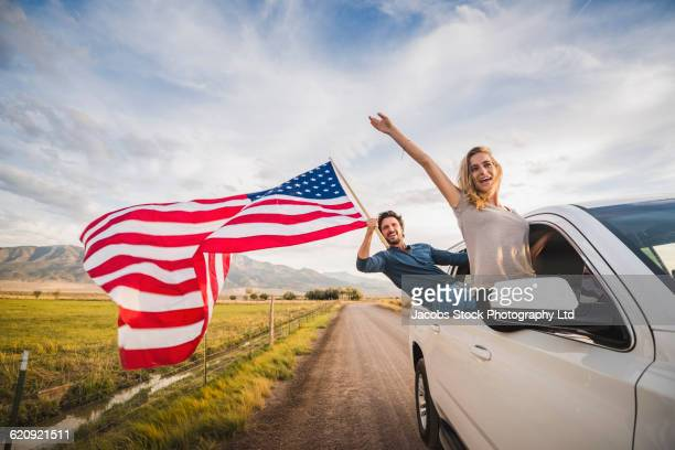 Hispanic couple waving American flag out car window