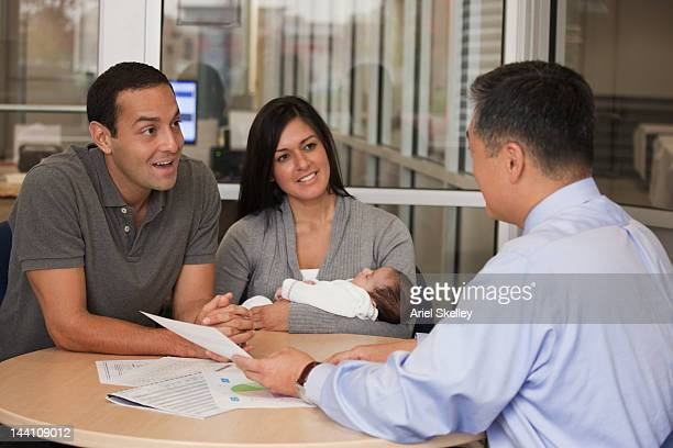 Hispanic couple with baby talking to financial advisor