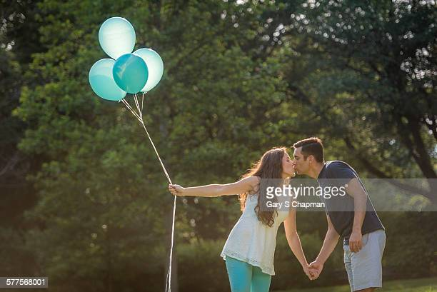 Hispanic couple with gender reveal balloons