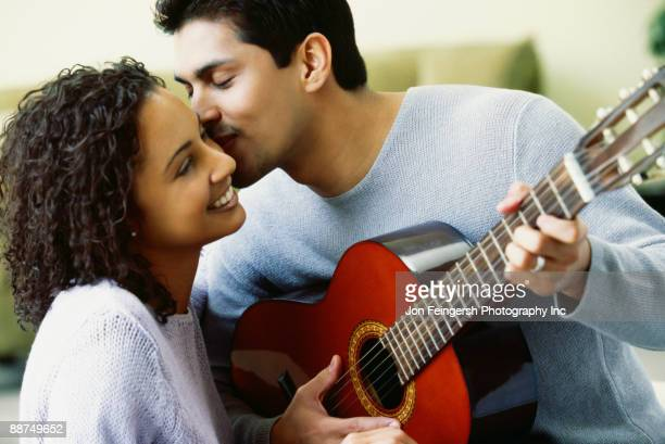 Hispanic couple with guitar kissing