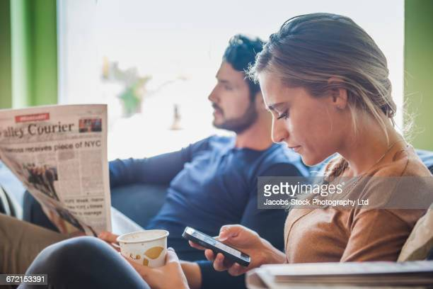 Hispanic couple with newspaper and cell phone in coffee shop