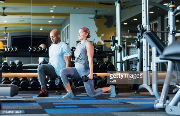 hispanic couple working out at the gym, doing lunges - side by side stock pictures, royalty-free photos & images