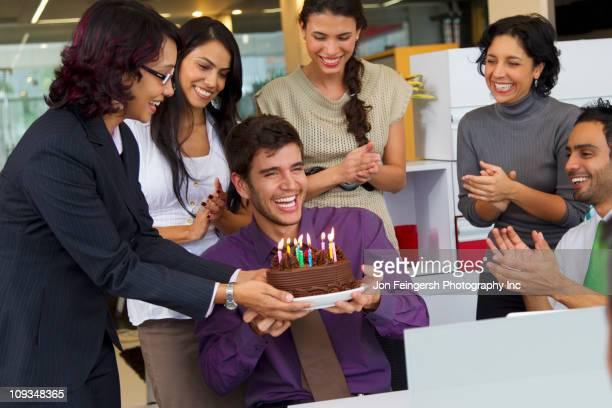 Hispanos colegas sorprendente ejecutivo con pastel de cumpleaños